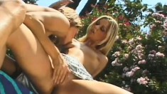 Two blonde beauties engaging in passionate lesbian action by the pool